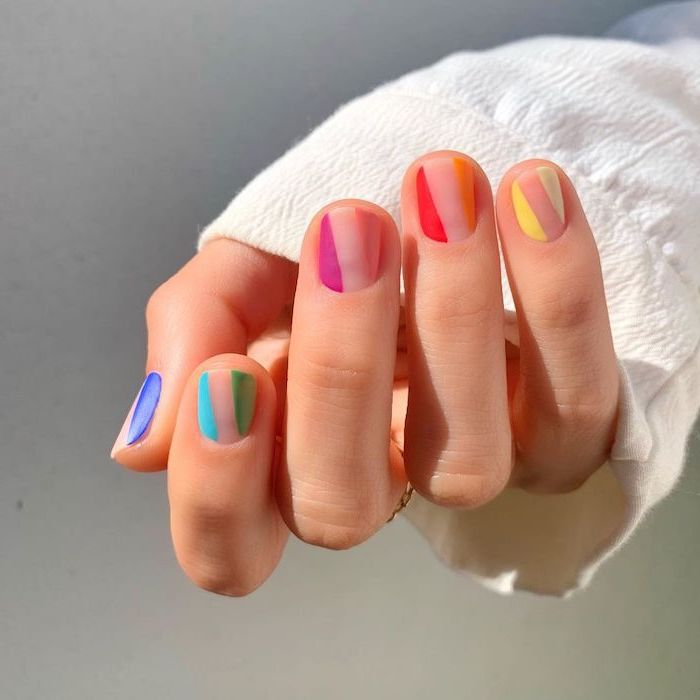 blue green pink orange yellow geometrical nail polish on nude short squoval nails almond shaped nails