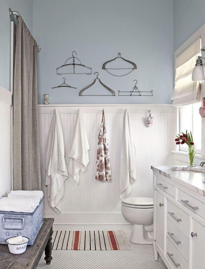 blue walls on top white shiplap on the bottom farmhouse bathroom tile white mosaic floor white vanity with marble countertop