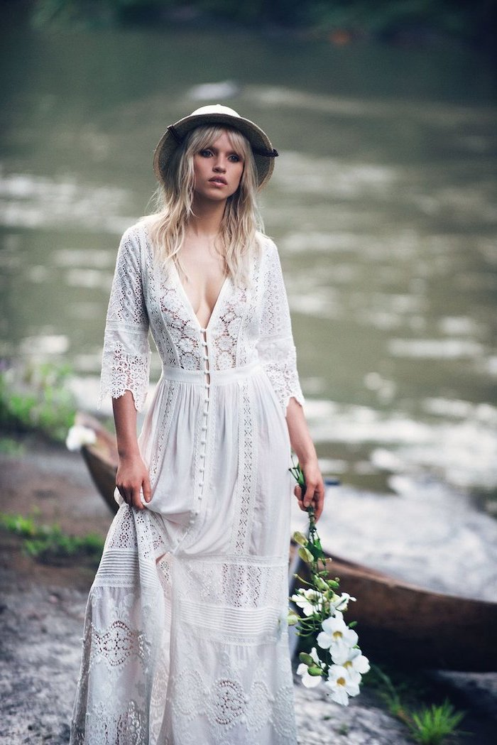 bohemian style wedding dresses blonde woman with bangs wearing all lace dress with buttons at the front hat holding white flower bouquet
