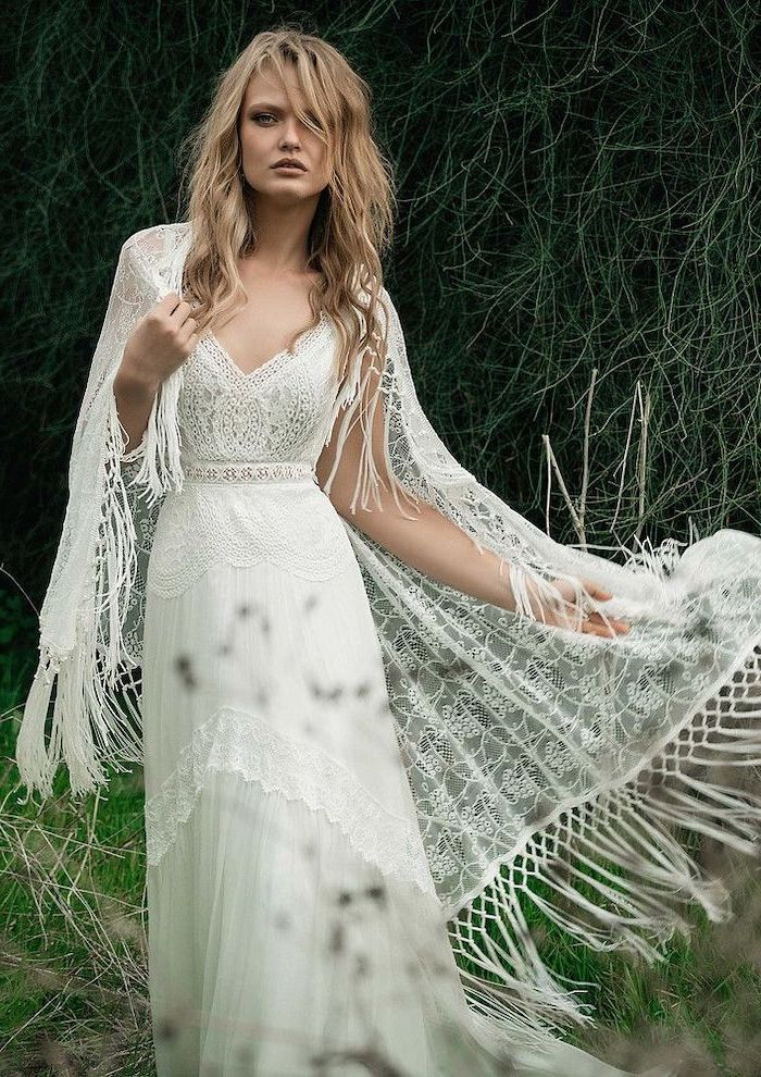 bohemian wedding dress blonde woman with shoulder length wavy hair wearing lace white dress with large white lace scarf