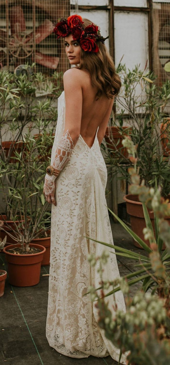 boho beach wedding dress woman with medium length light brown wavy hair wearing floral crown made of red roses long lacy dress with bare back