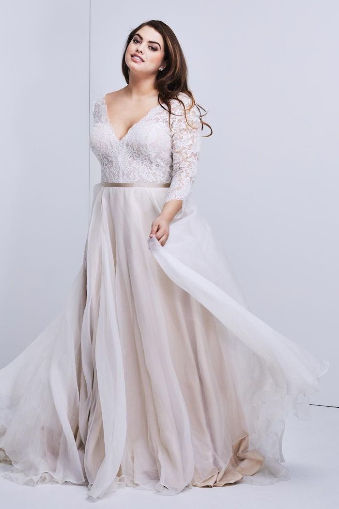 boho lace wedding dress woman with long wavy brown hair wearing long dress with lacy top with long sleeves bottom skirt made of tulle