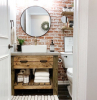 brick wall behind wooden vanity with open shelving round mirror above it farmhouse bathroom wall decor wooden shelves above the toilet