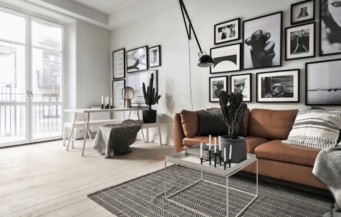 brown leather sofa black and white framed photos hanging on white wall scandinavian interior design black and white rug on wooden floor