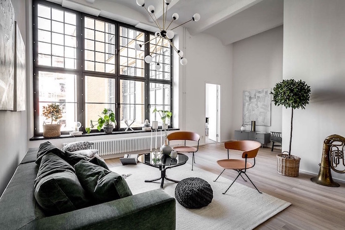 brown metal chairs green sofa black ottoman small round coffee table scandinavian minimalism all white walls