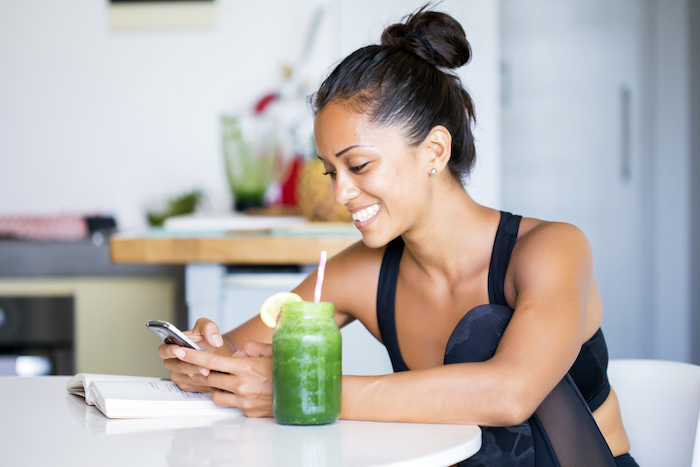 brunette woman sitting on a chair next to table best detox cleanse green smoothie book on the table