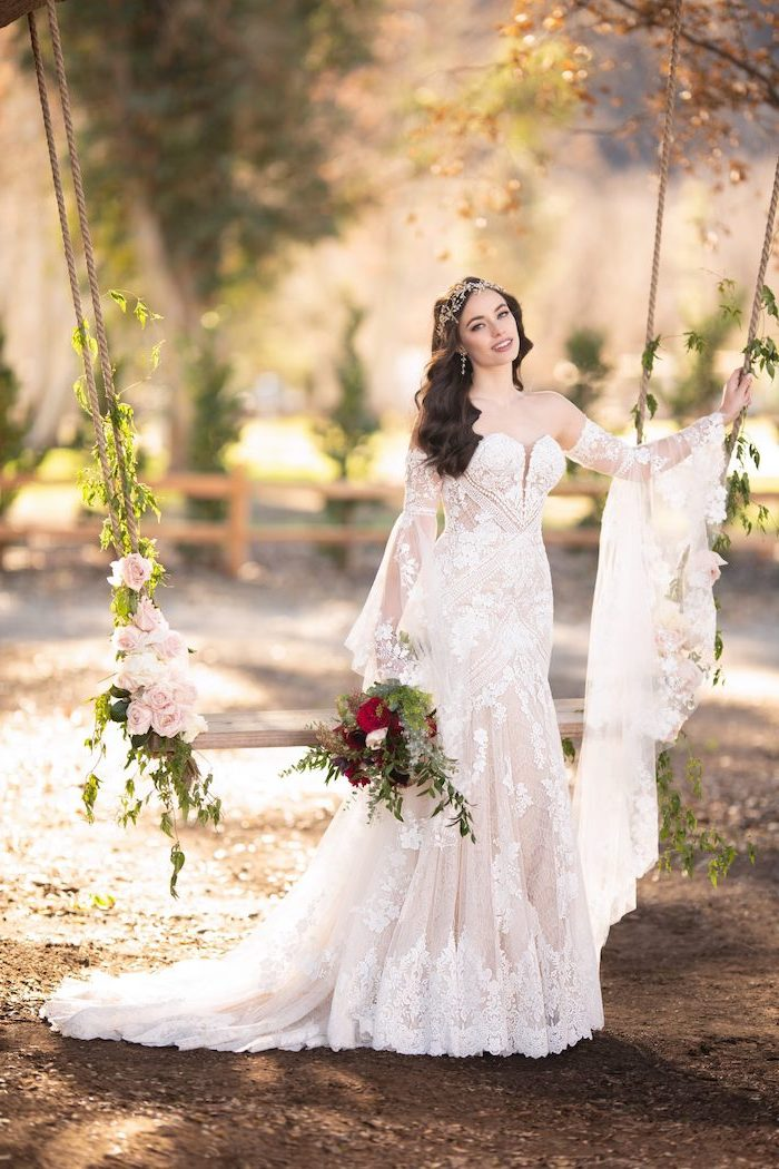 brunette woman wearing all lace dress with long sleeves bohemian wedding dress standing next to swing with flowers