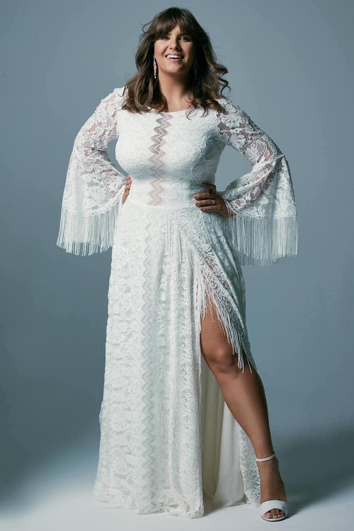 brunette woman with bangs wearing dress made of lace with fringe on the bottom of the sleeves bohemian style wedding dresses white sandals