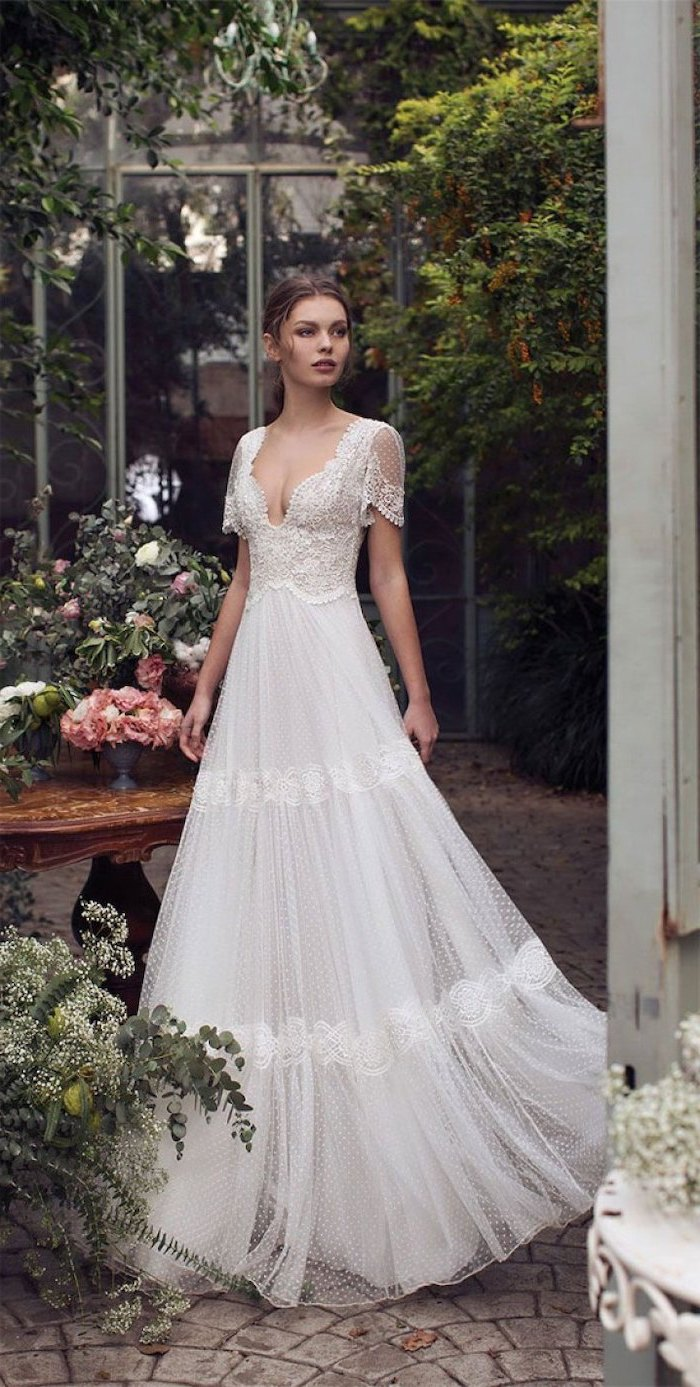 brunette woman with hair in low updo bohemian style wedding dresses wearing dress with short sleeves made of lace and tulle