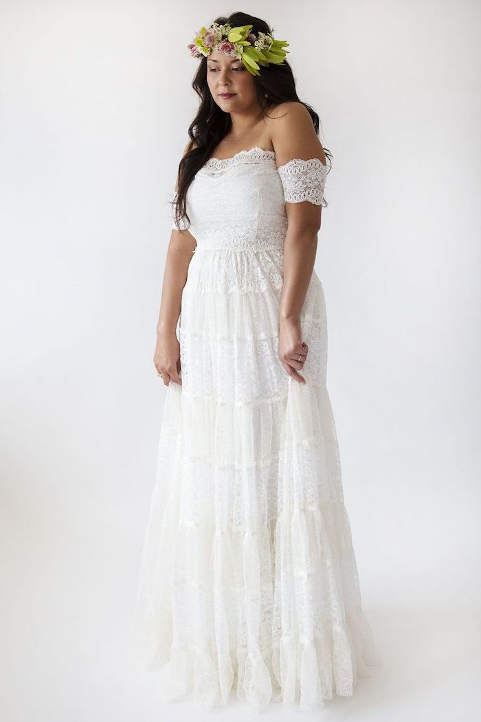 brunette woman with long wavy hair wearing flower crown boho lace wedding dress made of lace with short sleeves