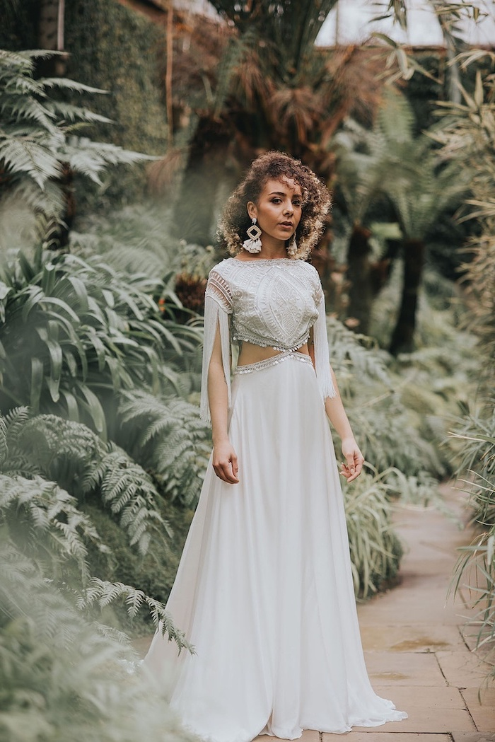 brunette woman with shoulder length curly hair wearing long flowy wedding dress with lacy top and bottom made of tulle