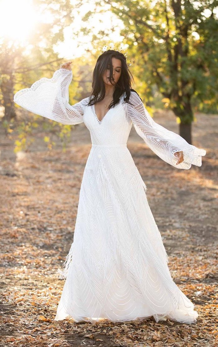 brunette woman with wavy shoulder length hair wearing all lace white unique wedding dresses with bell sleeves