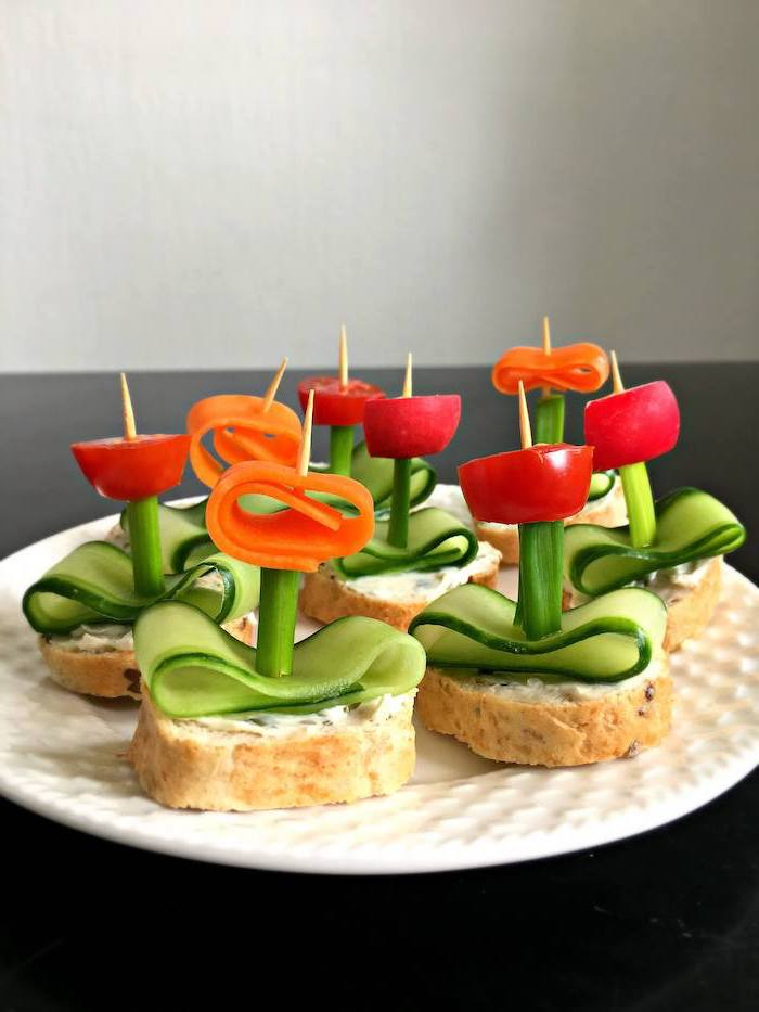bruschetta with cream cheese cucumber slices tomatoes carrots arranged on white plate vegan party food