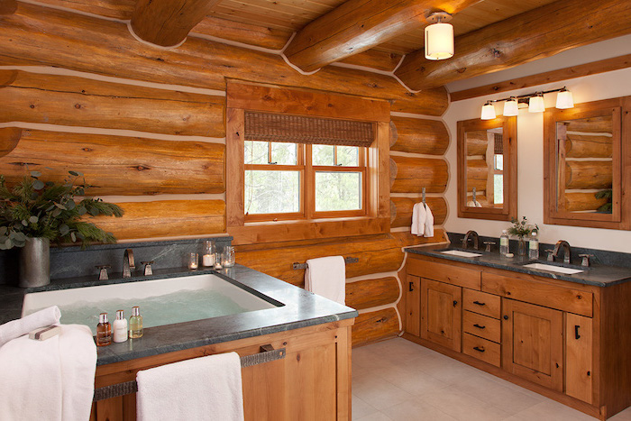 cabin decor walls and ceiling with wood beams bathroom decor signs wooden vanity with two sinks two mirrors black granite countertops