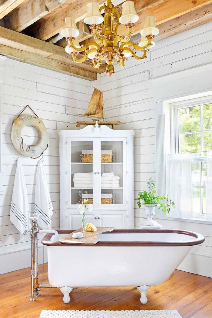 cabinet with towels in the corner vintage bath on wooden floor white shiplap on the walls exposed wood beams on the ceiling bathroom decor signs