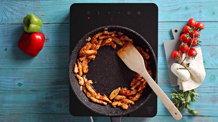 chicken cooking in black saucepan with wooden spatula traditional mexican food blue wooden surface with tomatoes and peppers
