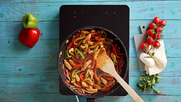 chicken cooking with onion and peppers in black saucepan with wooden spatula on blue wooden surface traditional mexican food