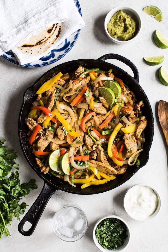 chicken fajitas cooked in black dish mexican food recipes with peppers onion garnished with lime slices and chopped fresh parsley