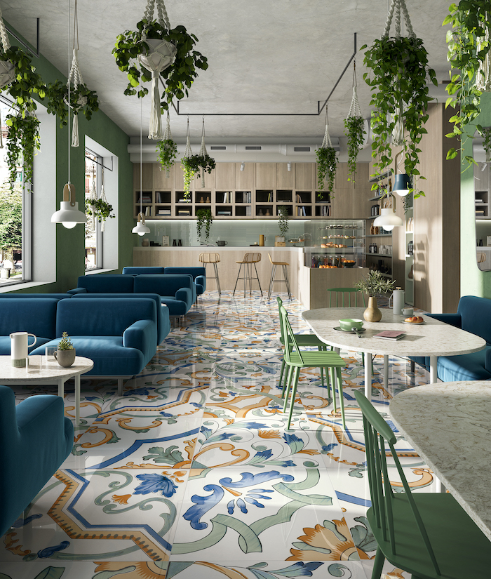 colorful tiles with floral print on the floor of restaurant with blue velvet sofas green chairs floor tiles plants hanging from the ceiling