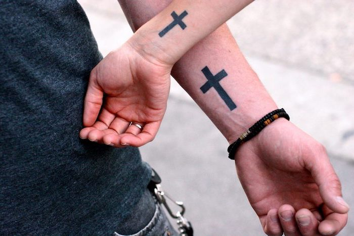 couples matching tattoos tattoos that represent growth two small black crosses on the wrists of man and woman