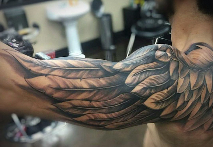 eagle wings upper arm sleeve tattoo starting from the back simple tattoos for men blurred background