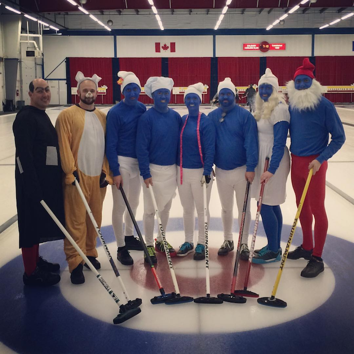 eight people dressed as characters from the smurfs standing on ice hockey ring halloween costume ideas for girls holding sticks