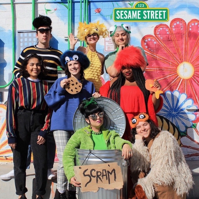 eight people dressed as the characters from sesame street trio halloween costumes posing in front of wall with grafitti