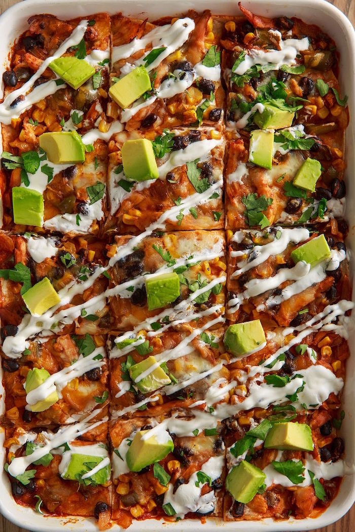 enchilada casserole with black beans corn mexican dishes white sauce on top chopped avocado