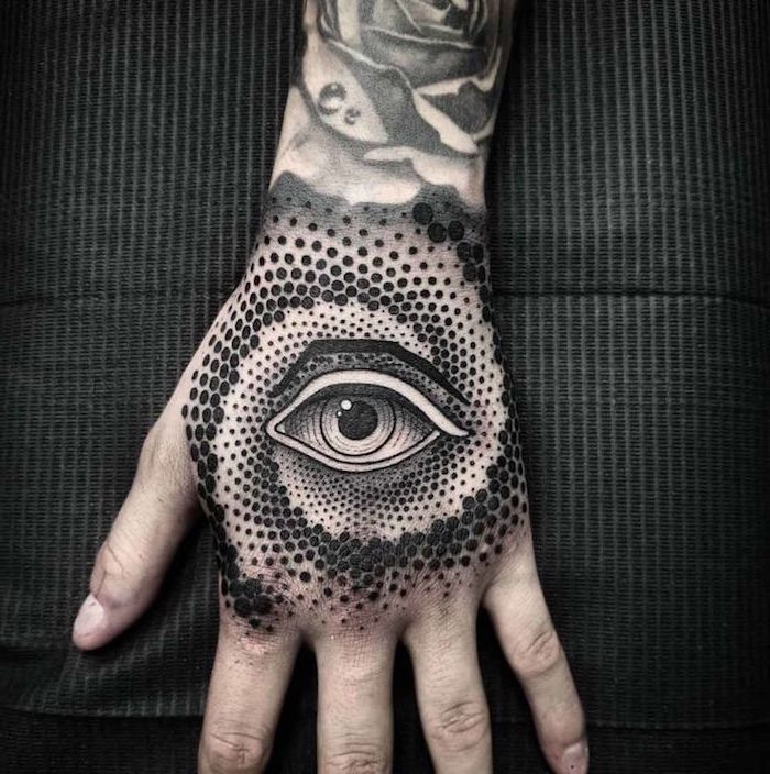 evil eye hand tattoo surrounded by dots in circular shape back tattoos for men black background