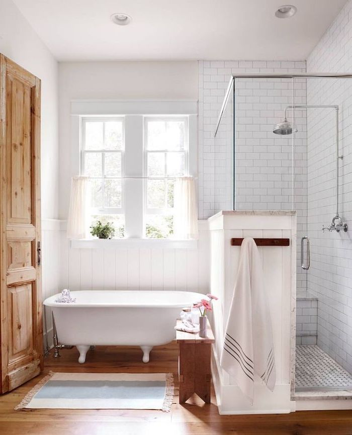 farmhouse bathroom ideas white subway tiles in the shower separate bath on wooden floor small rug next to it