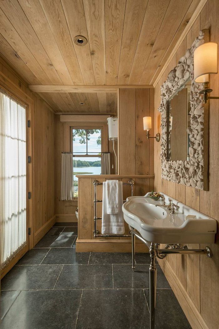 farmhouse bathroom shelves wooden shiplap ceiling and walls black tiles on the floor mirror above the sink with seashells covered mirror
