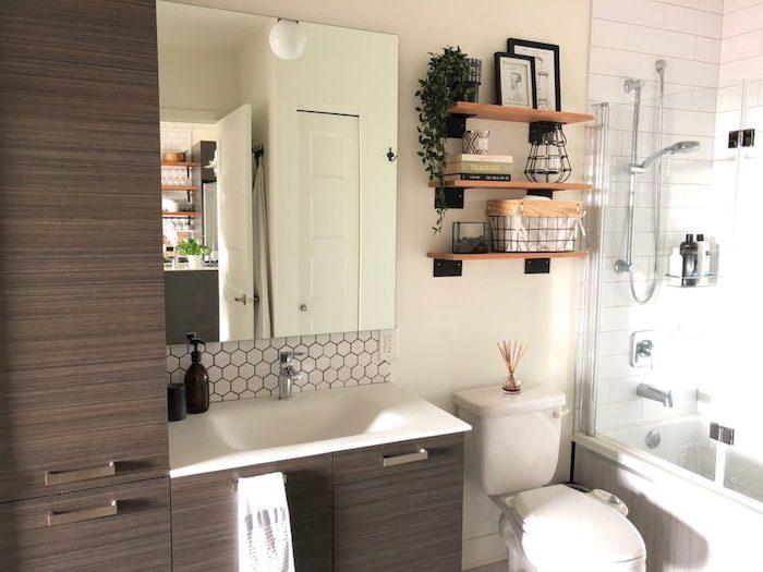 farmhouse bathroom tile dark wooden cabinets white sink mirror above it white subway tiles under the shower