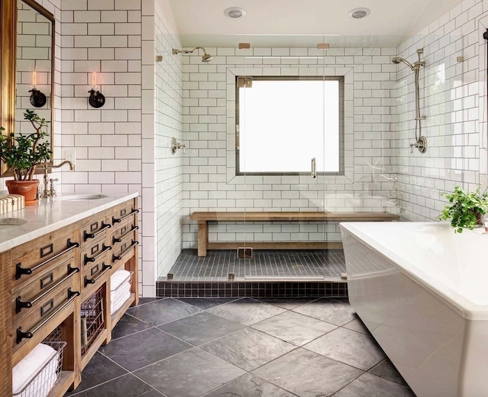farmhouse bathroom wall decor white subway tiles black tiles on the floor wooden vanity with two sinks marble countertop mirrors above the sink