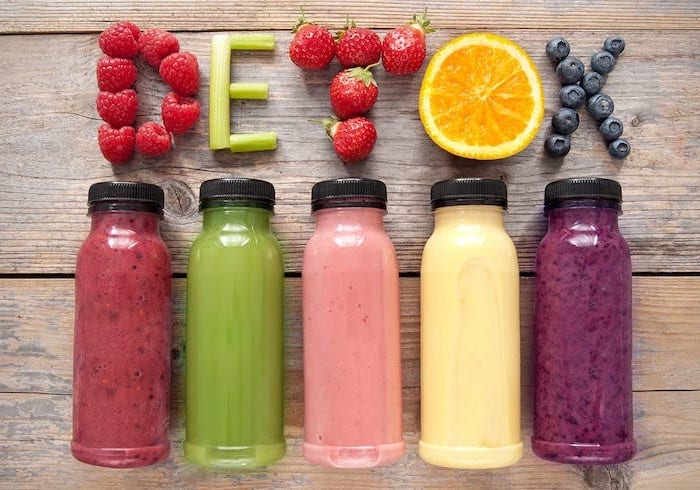 five bottles filled with smoothies in different colors how to detoxify your body detox written with fruits above them
