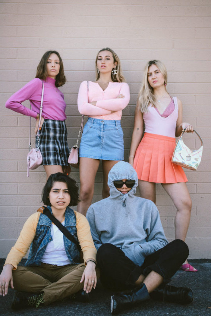 five people dressed as the characters from mean girls group halloween costumes photographed together in front of brick wall