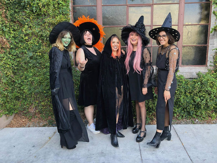 five women dressed as witches in all black cute group halloween costumes photographed on the sidewalk
