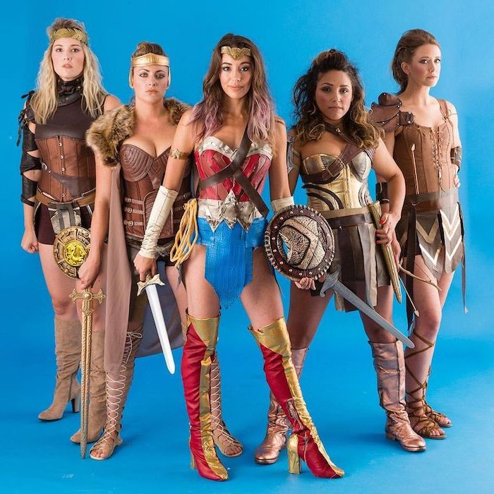five women dressed as wonder woman and the amazons cute group halloween costumes photographed in front of blue background