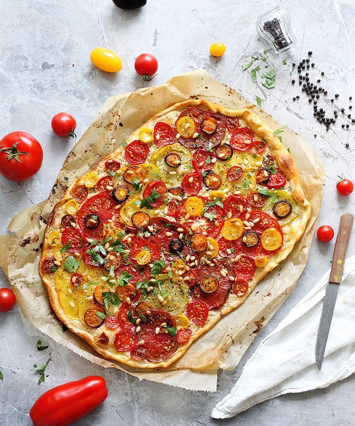 flatbread baked with different kinds of tomatoes olives pine nuts chopped basil vegan bites placed on white surface