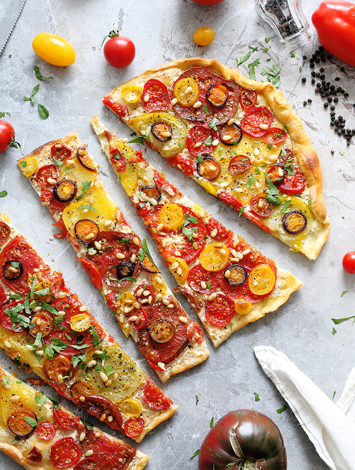 flatbread baked with different kinds of tomatoes pine nuts chopped parsley cut into pieces vegan finger food granite surface