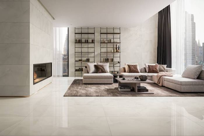 floor tiles all white tiles on the walls and floor large windows white corner sofa two bookshelves wooden coffee table