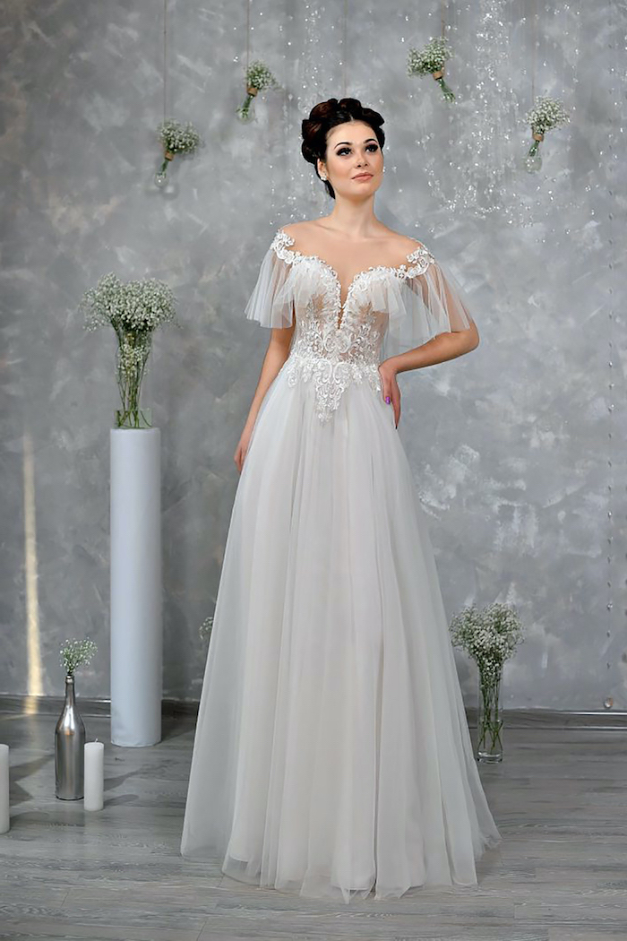 flowy wedding dress worn by woman with black hair in high updo bottom of the dress made of tulle