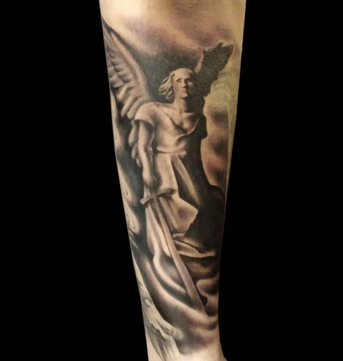 forearm tattoo of an angel holding a sword symbols with deep meanings black background
