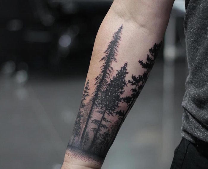 forest landscape with tall trees wrap around forearm tattoo small tattoo ideas for men wearing black jeans gray t shirt