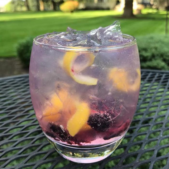glass filled with blackberry lemonade filled with ice detox drinks placed on black garden table
