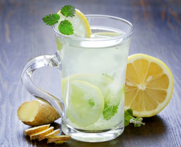 glass filled with water with lemon slices mint leaves ginger and lemon on the side what is detox placed on wooden surface