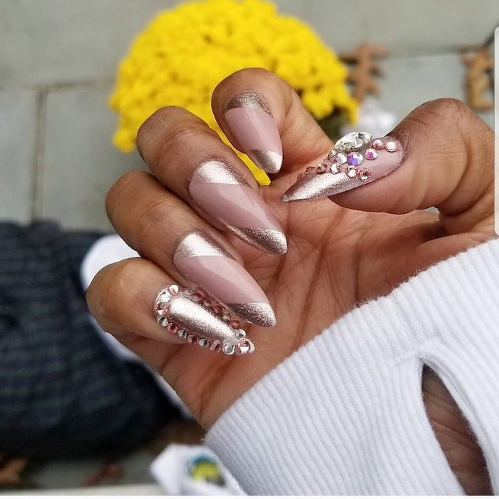 gold glitter with nude nail polish cute acrylic nail ideas rhinestone decorations on thumb and pinky finger