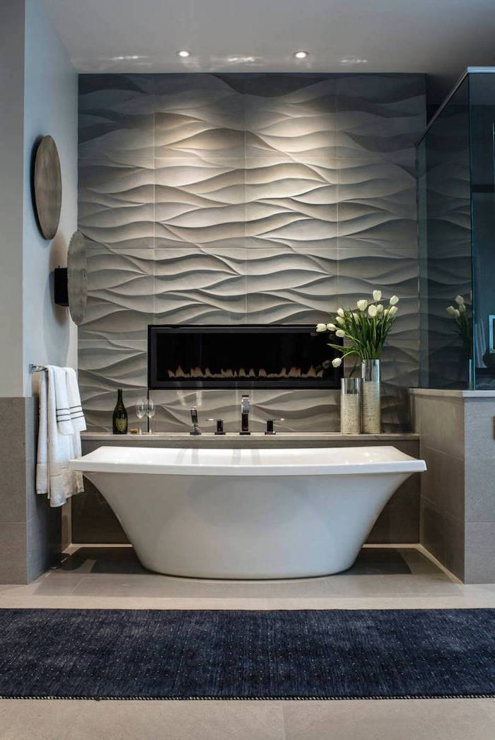 gray 3d tiles accent wall with fireplace behind the bathtub bathroom floor tiles beige tiles on the floor