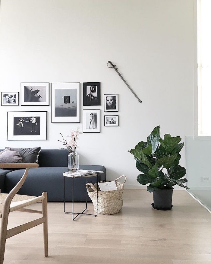 gray sofa framed black and white photos above it scandinavian decor wooden chair wooden floor small side table