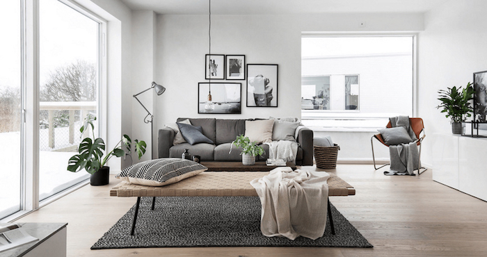 gray sofa with throw pillows black and white rug on wooden floor scandinavian interior design black and white frames photos on white wall