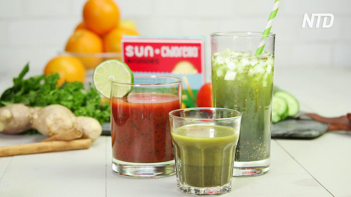 green and red smoothies in three glasses placed on white surface best detox cleanse fruits and vegetables in the background